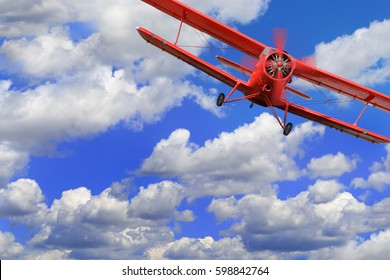 Red airplane biplane with piston engine flies and makes turn in cloudy sky