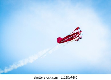 Red airplane with propellers and white smoke on the tail flying in the blue sky