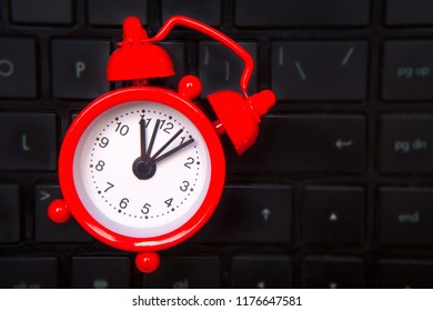 Red alarm clock, black keyboard, dark laptop