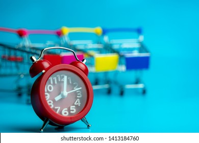 Red alarm clock with blurry lines of empty shopping troll cart on blue background use as online shopping or big sale event concpet