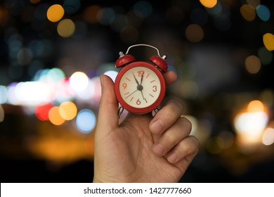 Red Alarm Clock with bokeh color lights background. De focused city lights at night.
