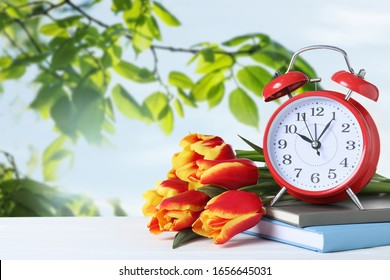 Red alarm clock, books and tulips on table against blurred background, space for text. Spring time