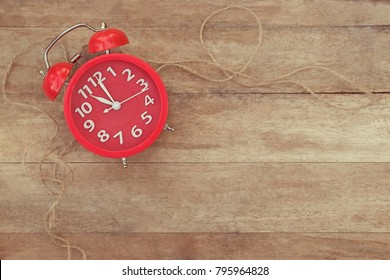 Red alarm clock with brown rope placed on the wooden table. Show time at eleven o'clock. Use for background and texture. Vintage and copy space.