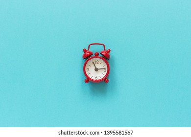 Red alarm clock in center on blue paper background. Minimal style Copy space Top view Template for your text, design.