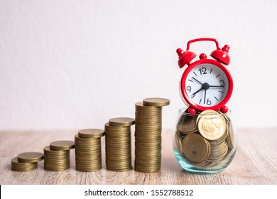Red alarm clock A coin in a glass bottle. Coin ladder, arranged from high to low. Time and financial risk concepts. Business investment should take appropriate time. Accounting and marketing.