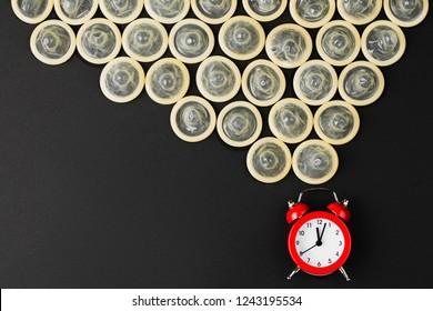 red alarm clock with condoms on black background, flat lay, concept of fight against HIV and aids