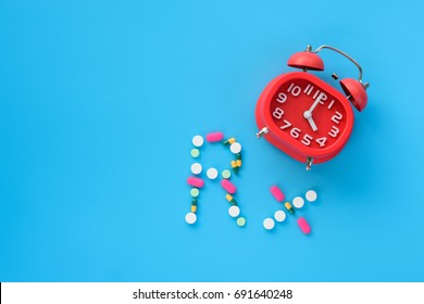 """A red alarm clock displaying four o'clock noon with pills in both tablets and capsules layout as text """"Rx"""" on blue background, medicine time concept"""