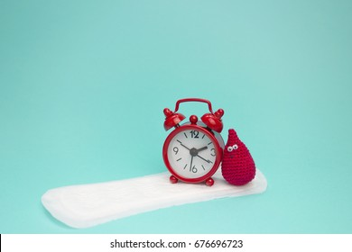 Red alarm clock, dreamy crochet blood drop and daily menstrual pad. Menstruation sanitary woman hygiene. Medical conception photo. Woman critical days, gynecological menstruation cycle