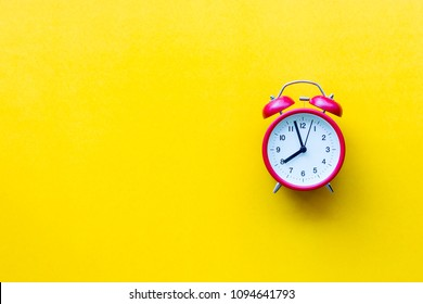 A red alarm clock with eight o'clock on yellow  background with copyspace