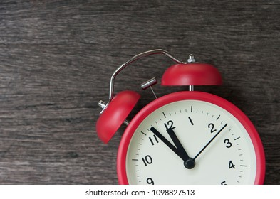 Red alarm clock with few minutes to twelve o'clock.