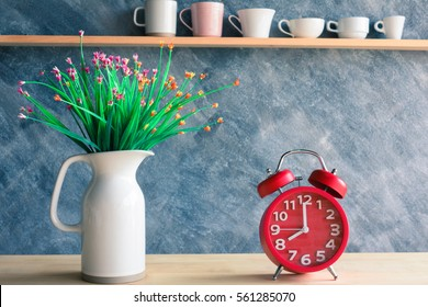 Red alarm clock with flower in jug on table and various cups background