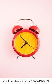 Red alarm clock with a fresh orange dial. Retro styre 'orange' clock with bells on pink background.