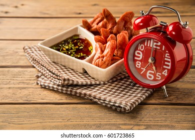 Red alarm clock with fried hot dog with sauce on wood table. Tha