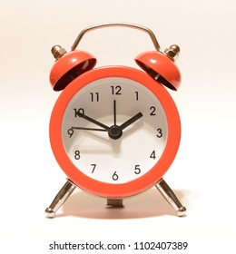 A red alarm clock isolated over white background.