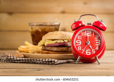 Red alarm clock, Kurobuta pork spicy burgers, glass of cola and