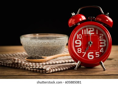 Red alarm clock with Lemon basil seeds on wood table. Healthy fo