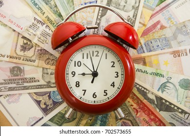red Alarm clock lie on dollars and different money bill of different lands . Time is money concept , idea, symbol. empty copy space for inscription or objects.