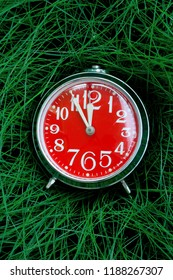 Red alarm clock in the meadow - It is high time