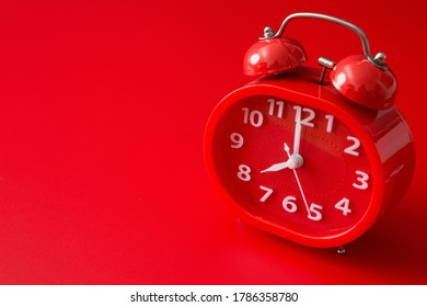 red alarm clock on a red background and copy space