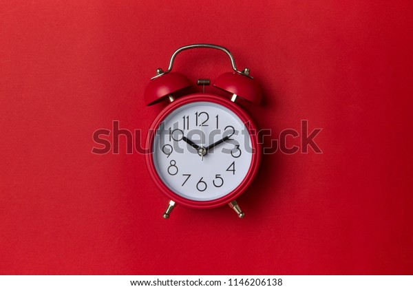 red alarm clock on red background. close up shot. top view.