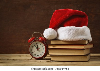 Red alarm clock. On the books Santa's hat, on a wooden background.