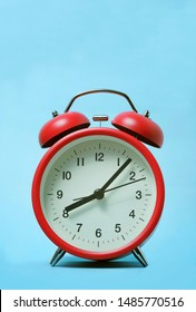 Red alarm clock on light blue color background