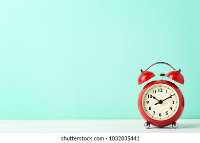 Red alarm clock on mint background