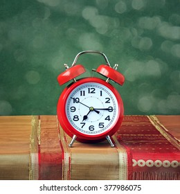 Red alarm clock on the table with a red tablecloth on the background of green.