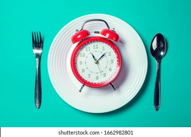 Red alarm clock on the white plate with spoon and fork on the color background. Food and diet concept