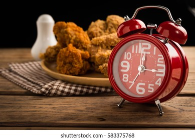 Red alarm clock on wood table with fried chicken background.