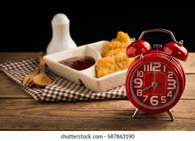 Red alarm clock on wood table with chicken nuggets background.