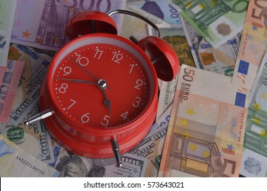 Red Alarm clock on world money Cash Currency Banknote Background Using for Time Concept