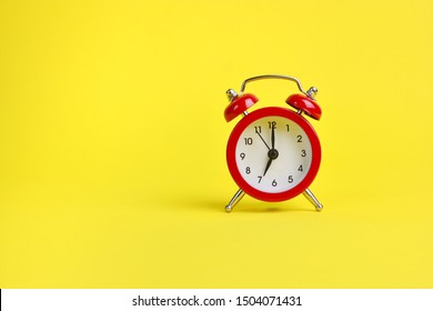 Red alarm clock on a yellow background. Copy space.