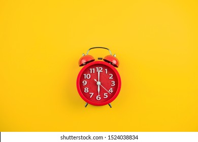 Red alarm clock on yellow background.