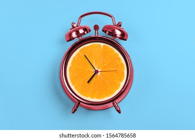 Red Alarm Clock With Orange- Time Concept and light blue background