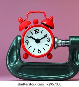 A red alarm clock placed in a Grey clamp against a pastel pink background, asking the question do you manage your time effectively?