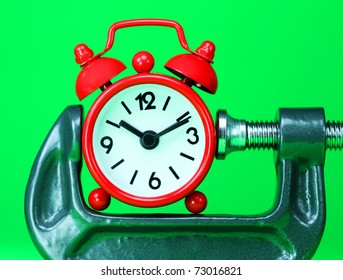 A red alarm clock placed in a Grey clamp against a pastel green background, asking the question do you manage your time effectively?
