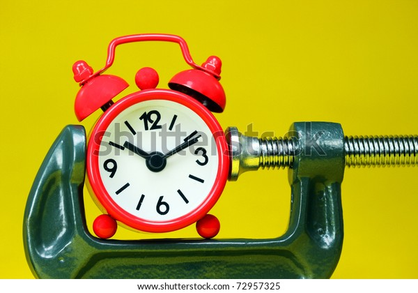 A red alarm clock placed in a Grey clamp against a pastel yellow background, asking the question do you manage your time effectively?