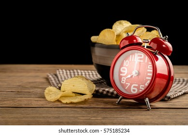 Red alarm clock with potato chips in cup on wood background.