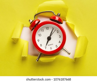 Red alarm clock showing up from torn yellow paper at white background. Time is our most precious resource concept. Bold design for inspirational poster or clothing print, copy space