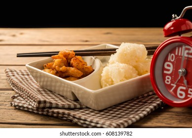 Red alarm clock, sticky rice and fried chicken on wood table.