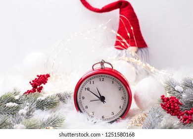 Red  alarm clock - symbol of  New Year, fir tree branches, berries,  gnome, balls  on white fur background. Winter holidays concept. Time concept. Top view. Copy space.