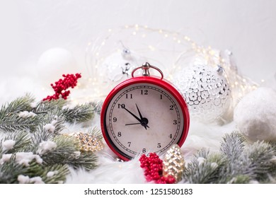 Red  alarm clock - symbol of  New Year, fir tree branches, berries, balls  on white fur background. Winter holidays concept. Time concept.  Copy space.