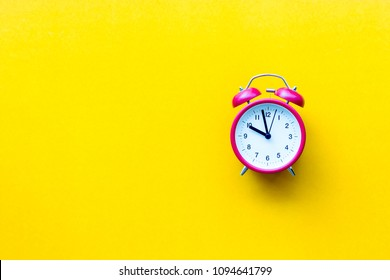 A red alarm clock with ten o'clock on yellow  background with copyspace