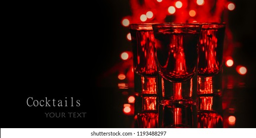 Red alcohol cocktails in shot glasses over red bokeh light and black background. Shots on bar counter in night club party.