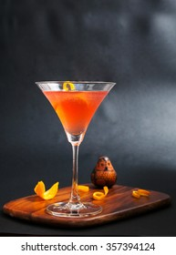 red alcohol cosmopolitan cocktail decorated with citrus lemon in martini cocktails glass on wooden cutting board isolated on a black background