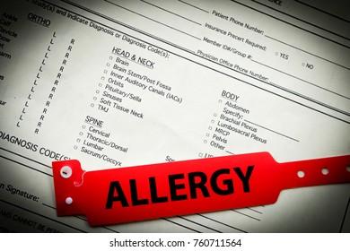 Red allergy bracelet on top of hospital paperwork