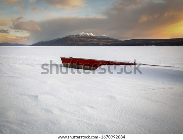 Red aluminum boat frozen into the lake with a snow capped mountain in the background.
