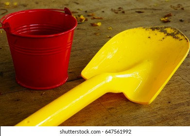 Red aluminum bucket and yellow plastic shovel toys for kids play in the garden