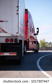 Red American powerful big rig semi truck with long reefer trailer transporting frozen cargo long haulage and turning on entrance to wide interstate highway